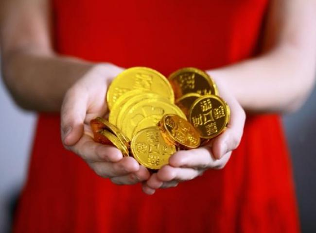 Lady in red holding gold coins